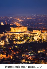 Acropolis and Parthenon, destination Athens Greece. Aerial, vertical view of illuminated rock at night. Ancient monument with lights on marble columns and hill, art, culture, civilization.