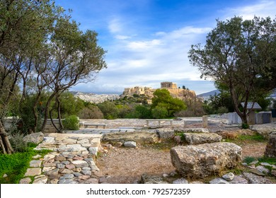 Acropolis with Parthenon. View through a frame of green plants, trees and ancient marbles, Athens, Greece.