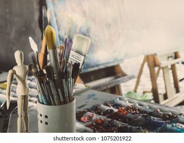 Acrylic Color in Palette, Brush, Wooden Figure,  Trowel on The Table and Canvas on the   easel in The Artist Studio