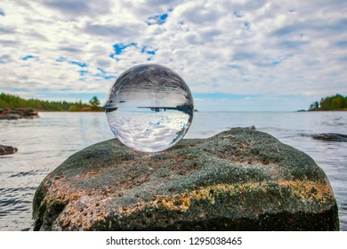 acrylic crystal ball on rock by a lake