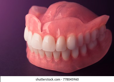 acrylic denture prosthesis of the upper and lower jaws of a man close-up on a black background