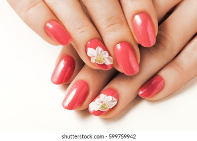 Acrylic red nails on hands and floral deign.