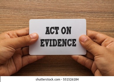 ACT ON EVIDENCE written on white card holding with two hands