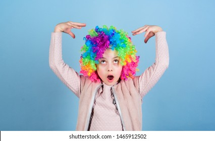 Acting school for children. Develop acting talent into career. Girl artistic kid practicing acting skills. Kid colorful curly wig artificial hair clown style blue background. Circus school concept.