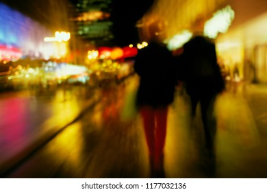 Action, blurry, in-motion view of two people walking through a brightly lit, wet, city street in Glasgow, Scotland.