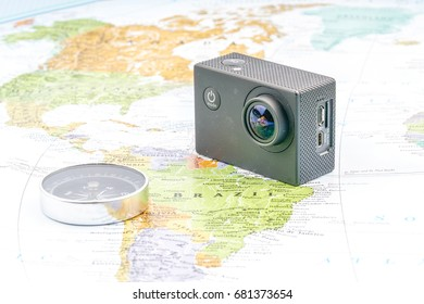 Action camera and compass with map background. Travelling concept