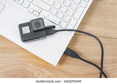Action camera connected to a white laptop, against the background of a wooden table