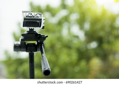 Action camera take video on the sky with green of leaf background on Tripod.