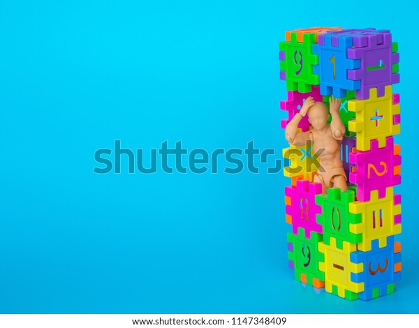 action figure standing in colorful plastic number and make a headache acting on blue background. Concept of education. copy space for text and content.
