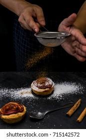 action of hand chef sprinkle ground cinnamon on pie apple rose form. dark food mood tone