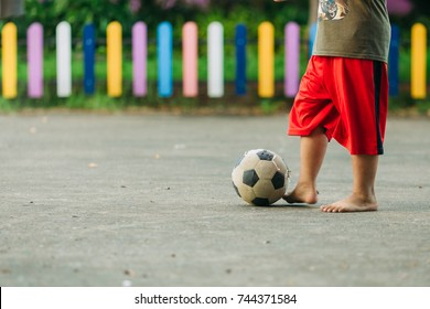 An action and motion picture of a ball and foot of a kid who is playing football in the sunshine day for exercise.