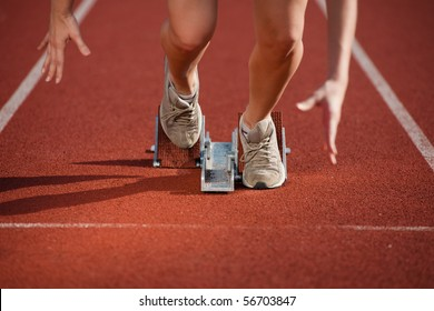 Action packed image of a female athlete leaving the starting blocks for a sprint run on a track