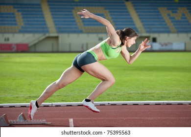 Action packed image of a female sprinter leaving starting blocks on the track. Side view.