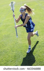 Action photo of a cute female Lacrosse player running on the grass field during a lacrosse game