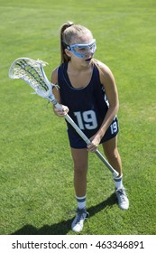 Action photo of a cute female Lacrosse player