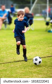 Action photo of young boy playing organized soccer