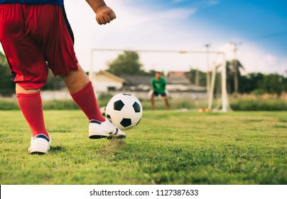 An action picture of a group of kid playing soccer football for exercise in community rural area under the sunset. Picture with copy space.