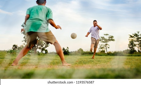 An action picture of a group of kid playing soccer football for exercise in community rural area under the sunset.