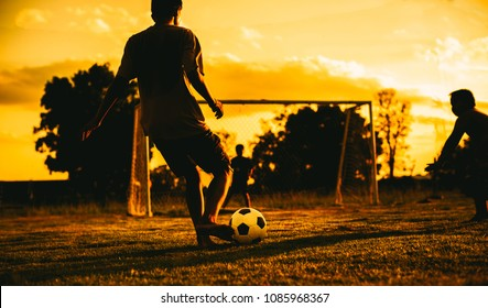 An action picture of a group of kids playing soccer football for exercise in community rural area under the sunset.