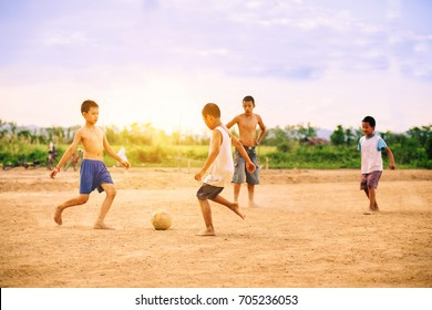 An action picture of a group of kids playing soccer football for exercise.