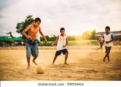 An action picture of a group of kids playing soccer football for exercise in community rural area.