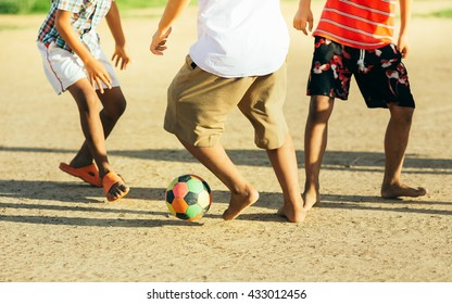 An action picture of the kids are playing soccer football in the sunshine day. Focus on the legs and ball.