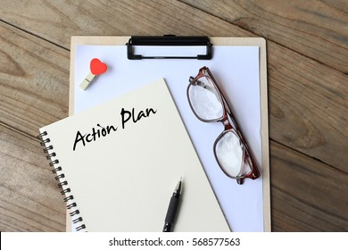 Action Plan - simple concept of text on notebook, clipboard, pen and glasses on wooden table. top view