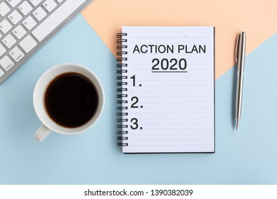 Action Plan text on Note Pad with alarm clock, smart phone, pen and potted plant