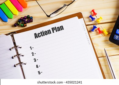 """Action plan"" text on paper in open diary with spectacles, colourful push pin, pen and calculator on the wooden table - business and finance concept"