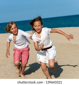 Action portrait of boy and girl having fun on beach chasing.