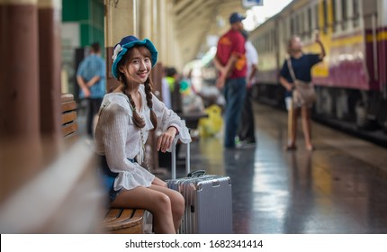 Action portrait a girl wearing a white dress and a hat  have fun and enjoyed at train station, holiday trip.