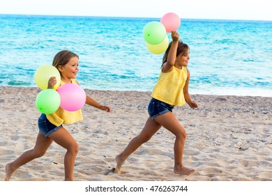 Action portrait of little girls chasing on beach with color balloons.