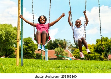 Action portrait of shouting African kids playing on swing in neighborhood.Out of focus houses in background.