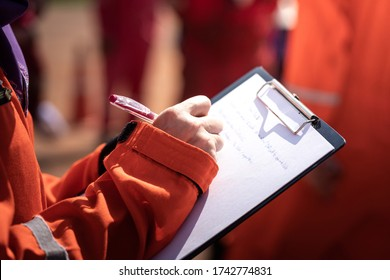 Action of safety officer or supervisor is taking note during operation audit in oil field activity, Close-up and selective focus at people's hand.