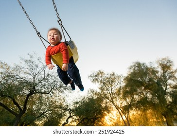 Action Shot of Baby on Playground Swing Against the Sky.