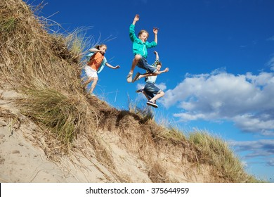 Action Shot Of Children Jumping From Sand Dune