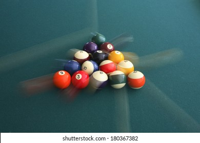 Action shot of cue balls on green billiards table