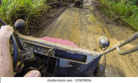 Action shot of driving a mud buggy on an off roading adventure through the jungle. First person perspective, point of view of the driver.