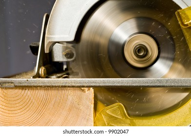 action shot of skilsaw cutting a board with sawdust flying