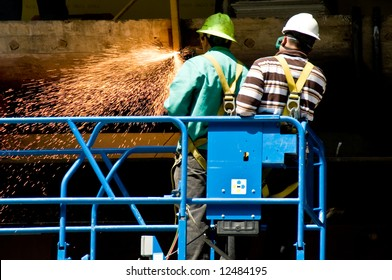 action shot of sparks flying while workers cut metal supports with a torch
