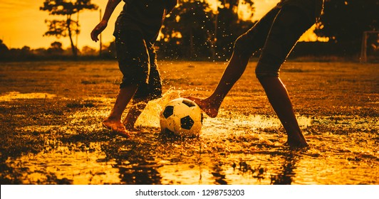 An action sport outdoors of a group of kids having fun playing soccer football for exercise in community rural area under the sunset.