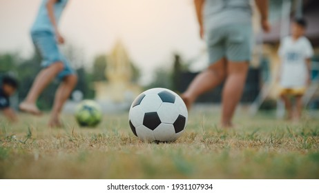 Action sport outdoors of a group of kids having fun playing soccer football for exercise in community rural area under the twilight sunset.