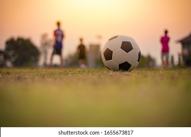 Action sport outdoors of kids having fun playing soccer football for exercise in community rural area under the twilight sunset sky. Picture with copy space.