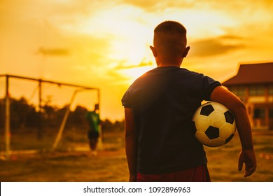 An action sport picture of a group of kid playing soccer football for exercise in before the sunset. Picture with copy space for world cup concept.
