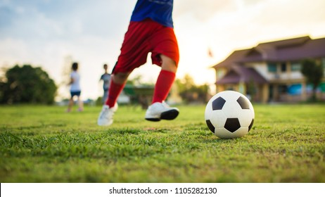 An action sport picture of a group of kid playing soccer football for exercise in community rural area under the sunset. Picture with copy space.