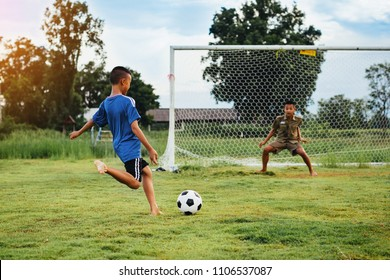 An action sport picture of a group of kid playing soccer football for exercise in community rural area under the sunset.