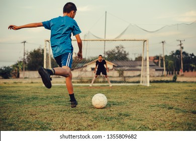 An action sport picture of a group of kids playing soccer football for exercise in the green grass field.