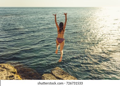 An action of a woman jumping from the rock into the blue sea. Summer Fun Lifestyle.
