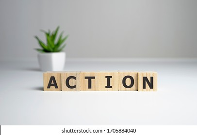Action word written on wood block. Action text on table, concept