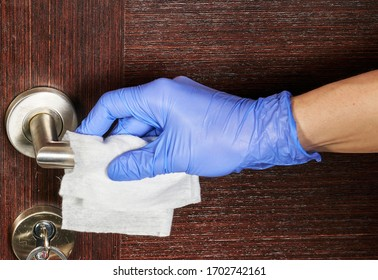 Actions to prevent the spread of coronavirus COVID-19, disinfection of the door handle. Hand in gloves wipes the door handle with a disinfectant